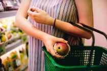 woman putting red apple on green shopping basket