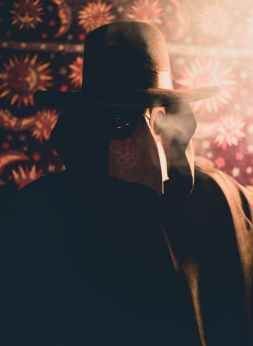 person in black coat and hat with plague doctor mask